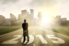 Businessman looking future 2015. Young businessman standing on the road and looking future 2015 Stock Photo