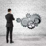 Businessman looking at  gears Royalty Free Stock Photos
