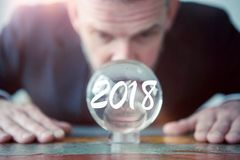Businessman looking at glass ball with the number 2018. Closeup of businessman looking at glass ball with the number 2018 royalty free stock photos