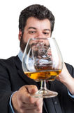 Businessman looking at a glass of whisky. Businessman looking a glass of whisky and drinking at the same time from a bottle Royalty Free Stock Images