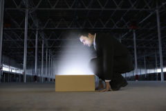 Businessman Looking At Glowing Box In Empty Warehouse Royalty Free Stock Photos