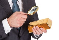 Businessman looking at gold bar through loupe Royalty Free Stock Photos