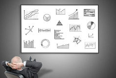 Businessman looking at graphical analysis concept. Relaxed businessman looking at graphical analysis concept on a whiteboard Stock Photos