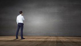 Businessman looking at grey wall