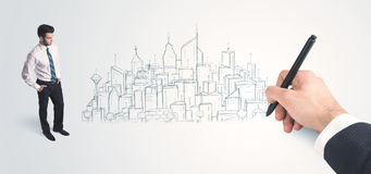Businessman looking at hand drawn city on wall Stock Photo