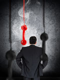 Businessman looking at hanging telephone receiver Stock Photos