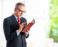 Businessman looking at his agenda. Portrait of a successful handsome businessman looking at his agenda Stock Photos