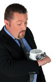 Businessman. Looking at his enormous hand watch Royalty Free Stock Photo