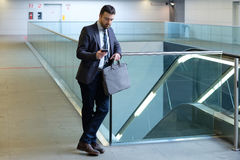 Businessman is looking at his mobile phone Stock Photo