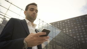 Businessman looking at his phone and waiting for someone outside the building. Business, technology and business people concept - serious businessman with