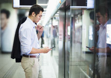 Businessman looking at his phone and waiting for the subway in Beijing Royalty Free Stock Image