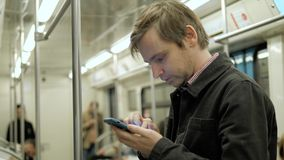 Businessman looking at his phone and waiting for subway in train stock images