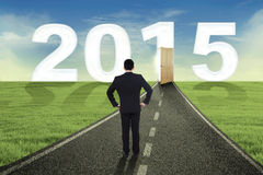 Businessman looking his vision in the future. Businessman standing on the road and looking at the door to future 2015 Royalty Free Stock Photography
