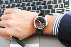 Businessman looking at his watch being too late. Businessman looking at his watch suggesting being late Stock Image