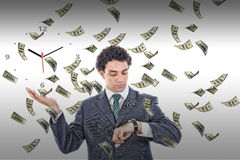 Businessman looking at his watch with money rain around him
