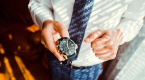 Businessman looking at his watch punctuality. Businessman puts expensive watches.Businessman checking time stock image