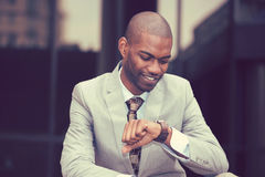 Businessman looking at his watch sitting outdoors Stock Photography