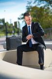 Businessman looking at his watch while sitting in the park Royalty Free Stock Image