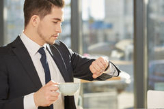 Businessman looking at his watch. Timing is everything. Handsome young businessman checking time on his watch holding a cup of coffee royalty free stock photos