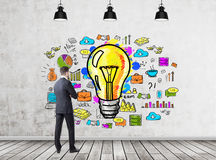 Businessman looking at idea icons. Rear view of a businessman in a dark suit looking at a bright idea drawing on a concrete wall in a room with three ceiling Royalty Free Stock Images