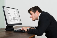 Businessman Looking At Invoice On Computer Royalty Free Stock Photography