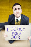 Businessman looking for a job. Young businessman holding sign Looking for a job from above Royalty Free Stock Photo