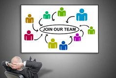 Businessman looking at join our team concept. Relaxed businessman looking at join our team concept on a whiteboard stock photos