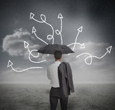 Businessman looking at jumble up arrows. Holding umbrella in dark grey landscape Stock Photos