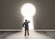 Businessman looking through a keyhole shape door Royalty Free Stock Photography