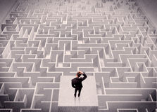 Businessman looking at labirynth from above. A confused businessman thinking while standing on a square platform above a detailed maze Stock Image