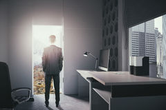 Businessman looking at landscape. Businessman standing in modern office interior with open door looking at landscape. Concept of choice between career Stock Images