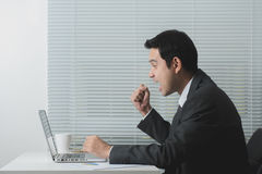 Businessman looking at laptop computer and raising his fist with delighted feeling Royalty Free Stock Photo