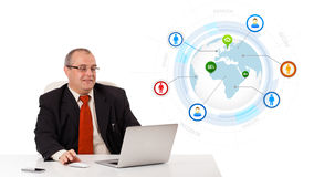 Businessman looking laptop with globe Stock Photo
