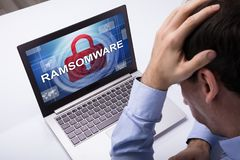 Businessman Looking At Laptop With Ramsomware Word On The Screen stock images