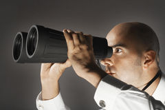 Businessman Looking Through Large Binoculars. Closeup of a businessman looking through large binoculars against gray background Stock Photography