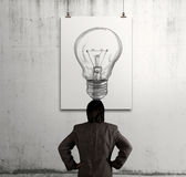 Businessman looking at light bulb in art frame Royalty Free Stock Photography