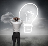 Businessman looking at light bulb with hands on head Royalty Free Stock Images