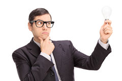 Businessman looking at a light bulb and thinking royalty free stock images