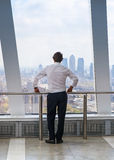 Businessman looking at London through the window Stock Photo