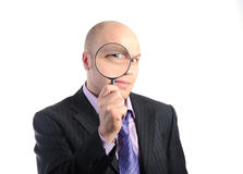 Businessman looking through a magnifying Stock Photo