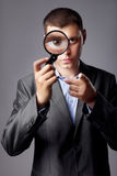 Businessman looking through a magnifying glass Royalty Free Stock Photography