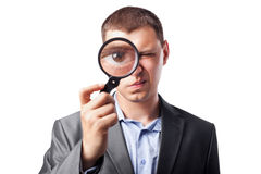 Businessman looking through magnifying glass Stock Photography