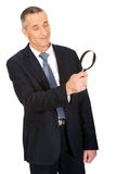 Businessman looking through a magnifying glass Royalty Free Stock Image