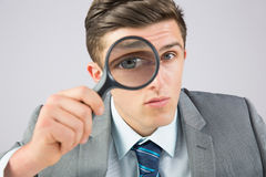 Businessman looking through magnifying glass Stock Photo