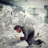 Businessman looking with magnifying glass in the middle of a flood of sheets. Legal agreements and contract clauses. Concept of bureaucracy and quibbles stock photo