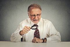 Businessman looking through a magnifying glass Stock Photos