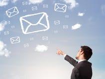 Businessman looking at mail symbol clouds Stock Photos