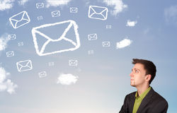 Businessman looking at mail symbol clouds Royalty Free Stock Photography