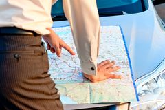 Businessman looking  at a map spread out on the hood of a car Royalty Free Stock Images