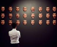 Businessman looking at mask. And selecting his mood Stock Photo